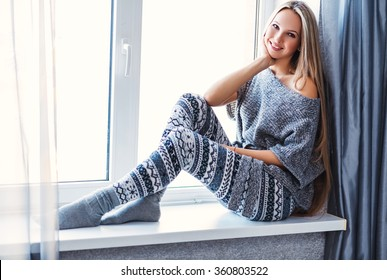 Young beautiful happy woman wearing knitted nordic print clothes sitting home by the window.