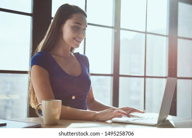 Young beautiful happy woman while working in office using laptop computer