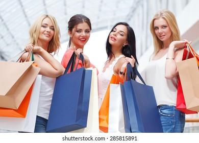 Young beautiful happy women showing shopping bags in mall