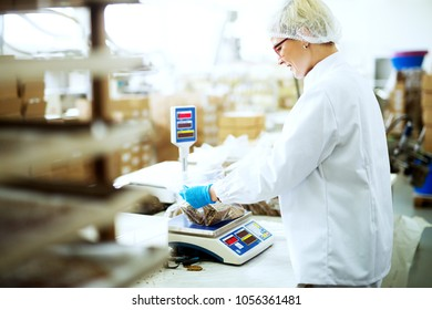 Young beautiful happy worker is carefully measuring healthy food snacks before packing it in a food industry factory.