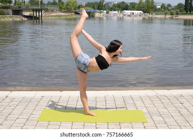 Young beautiful healthy woman practicing yoga and doing meditation at public park.