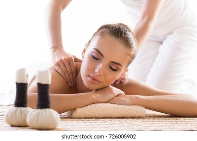 Young, beautiful and healthy woman relaxing in spa salon. Traditional oriental aroma therapy and massaging treatments with herbal balls.