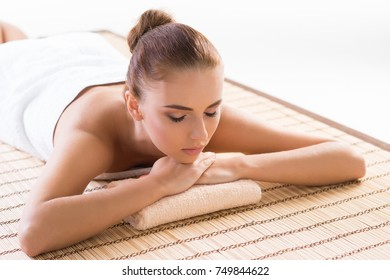 Young, beautiful and healthy woman relaxing in spa salon. Traditional oriental therapy and massaging treatments.