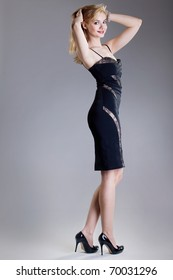 young beautiful high blonde in a black dress and shoes on a high heel