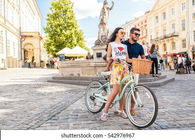 young beautiful hipster couple in love walking with bicycle on old city street, summer Europe vacation, travel, fun, happy, smiling, sunglasses, trendy outfit, romance, date
