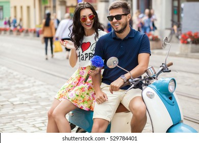 young beautiful hipster couple riding on motorbike city street, summer europe vacation, traveling, romance, smiling, happy, having fun, sunglasses, stylish outfit, together in love, adventures, date