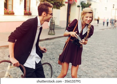 Young beautiful hipster couple vintage style posing outdoor on the street fashion style having fun together laughing