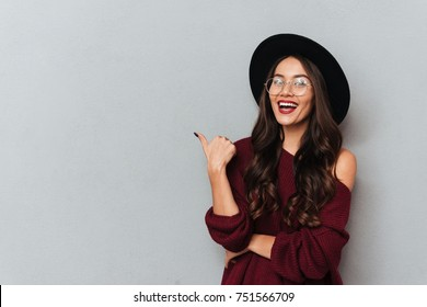 Young beautiful hipster girl showing thumb up gesture, looking at camera, isolated on gray background