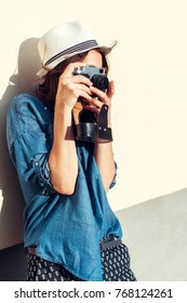 young and beautiful hipster pretty woman posing outdoor on the street in summer with camera, make photos and feels happy