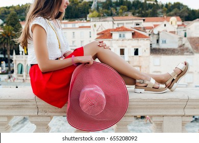 young beautiful hipster stylish woman traveling in Europe, old city center, red skirt, hat, summer vacation, fashion trend, long legs, skin, golden metallic sandals, close up details, accessories