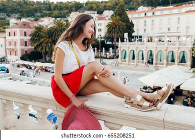 young beautiful hipster stylish woman traveling in Europe, old city center, red skirt, hat, summer vacation, fashion trend, long skinny legs, skin, sandals, smiling happy, positive, having fun