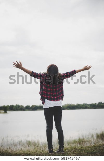 Young beautiful hipster woman in a field at sunset. Freedom enjoying with nature.