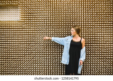 Young beautiful hipster woman in glasses and denim jacket against the background of an unusual wooden wall.