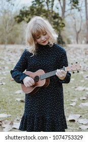 Young beautiful hipster woman in the park playing ukulele and smilling.Vintage tone