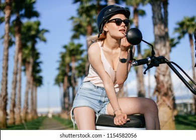 young beautiful hipster woman posing with bicycle on beach alley, applying lipstick on lips, looking at mirrow. Summer vacation, vintage style, boho outfit, blue dress, slim body, bright, colorful