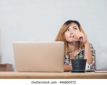 young beautiful hipster woman sitting on workplace and thinking about her work.