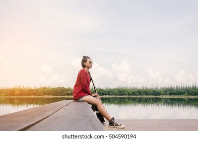 Young beautiful hipster woman sitting on the lake pier, Relaxed atmosphere, summer.