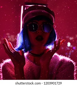Young beautiful hipster woman in street style fashion winter concept wearing gold hat cap and round sunglasses in pink neon light under snowflakes