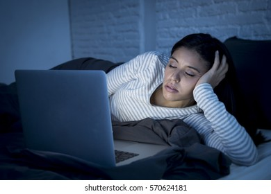 young beautiful hispanic internet addict woman in pajamas on bed at home bedroom asleep while working with laptop computer late at night in dark room light just exhausted falling sleep