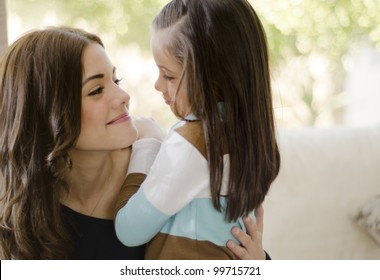 Young beautiful hispanic mother and daughter looking at each other and smiling