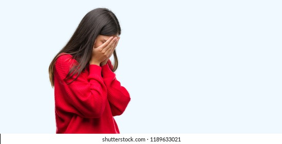 Young beautiful hispanic wearing red sweater with sad expression covering face with hands while crying. Depression concept.