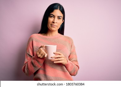 Young beautiful hispanic woman drinking a cup of hot coffee over pink isolated background with a confident expression on smart face thinking serious