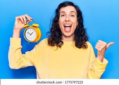 Young beautiful hispanic woman holding alarm clock pointing thumb up to the side smiling happy with open mouth