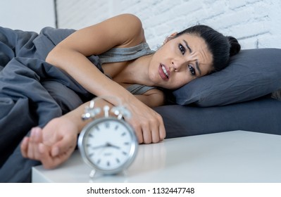 young beautiful hispanic woman at home bedroom lying in bed late at night trying to sleep suffering insomnia sleeping disorder or scared on nightmares looking sad worried in mental health concept
