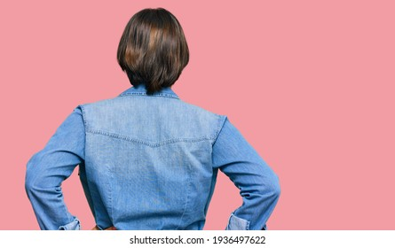 Young beautiful hispanic woman with short hair wearing casual denim jacket standing backwards looking away with arms on body