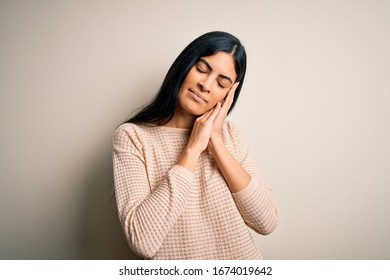 Young beautiful hispanic woman wearing elegant pink sweater over isolated background sleeping tired dreaming and posing with hands together while smiling with closed eyes.