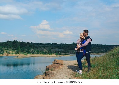 Young beautiful hugging couple stands on the Lake shore