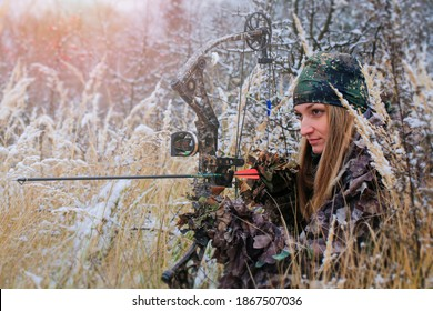 A young beautiful Hunter woman in camouflage in snowy forest with hunting bow in her hand. Winter lanscape. Copy space for text.