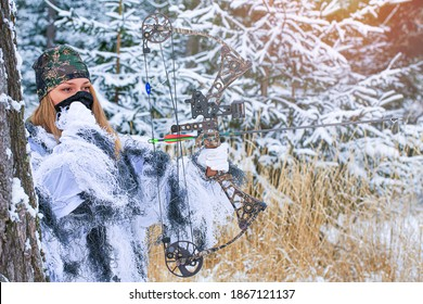 A young beautiful Hunter woman in winter camouflage in snowy forest with hunting bow in her hand.