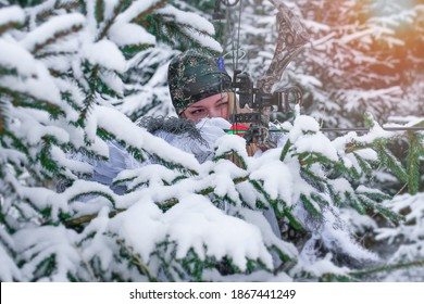 A young beautiful hunter woman in winter camouflage with hunting bow in her hand. All around are snowy trees.