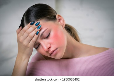 Young beautiful ill sick woman is suffering from heat, high temperature, headache and migraine, holding hand on forehead. Symptoms of the coronavirus, covid-19. Dangerous sunburn. Red face, blushing.