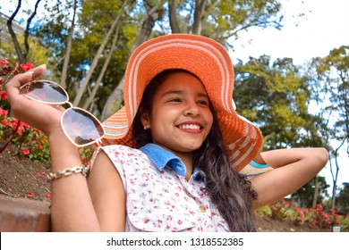 Young, beautiful and impressive, this is how this beautiful Latina looks with her wide smile contemplating all her suitors to whom she has arrows. She wears a dress, a sun hat and sunglasses.
