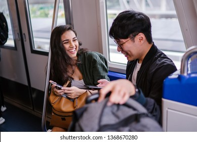 A young and beautiful Indian Asian woman is laughing as she views a video with her Korean male companion. They are sitting in a train during the day and are both smiling happily.
