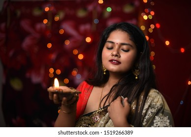 An young and beautiful Indian Bengali woman in Indian traditional dress is holding a Diwali diya/lamp in her hand standing in front of colorful bokeh lights. Indian lifestyle and Diwali celebration