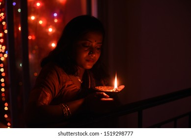 An young and beautiful Indian Bengali woman in Indian traditional dress is holding a Diwali diya/lamp in her hand standing on a balcony in darkness. Indian lifestyle and Diwali celebration