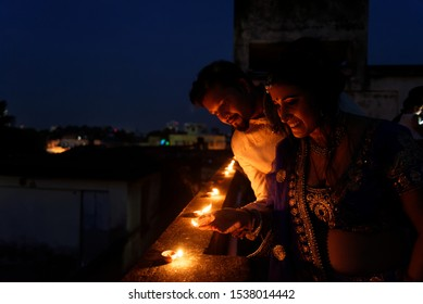 Young and beautiful Indian Gujarati couple in Indian traditional dress lightening Diwali diya/lamps sitting on the terrace in blue hour on Diwali evening. Indian lifestyle and Diwali celebration