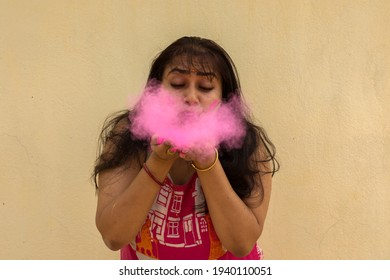 A young beautiful Indian lady playing with holi powder colors. Selective focus with yellow background.