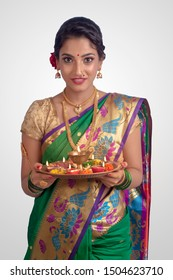 An young and beautiful Indian Maharashtrian woman in Green traditional ethnic saree holding a puja thali. Indian culture, religion and fashion