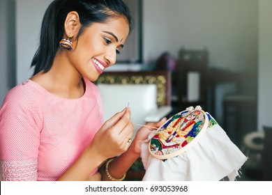 young beautiful indian woman doing embroidery
