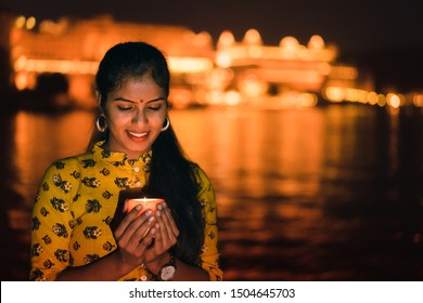 Young beautiful Indian woman holding a lit candle for Indian Festival Diwali at Ambrai Ghat in front of Picola Lake and City Palace, Udaipur, Rajasthan, India.