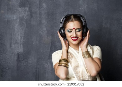 Young beautiful Indian woman listening to music on headphones
