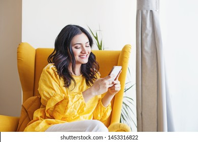 Young beautiful Indian woman using her mobile phone while sitting in the armchair at home
