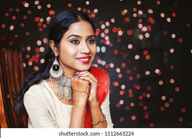 Young beautiful indian woman wearing jewelry and festive ethnic clothes sitting and waiting over bokeh background