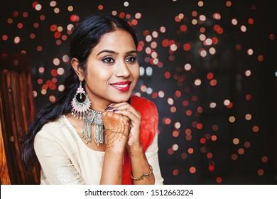 Junge schöne indianische Frau mit Schmuck und festlichen ethnischen Kleidung, sitzend und wartend auf Bokeh-Hintergrund