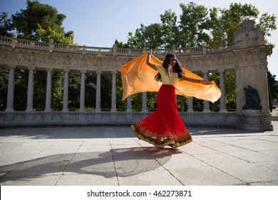 Young beautiful indian woman wearing traditional indian clothes, dancing bollywood dance outdoors