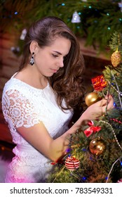 young, beautiful, intelligent girl with a gift for Christmas, sits on the background of Christmas tree, Christmas clock and a fireplace